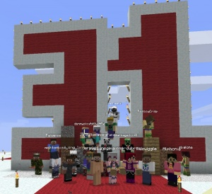 A group photo of members of the MindCrack and MindCrack Fan Servers celebrating Guude's 31st birthday in 2012. The photo was taken on top of a giant cake built for Guude's birthday.